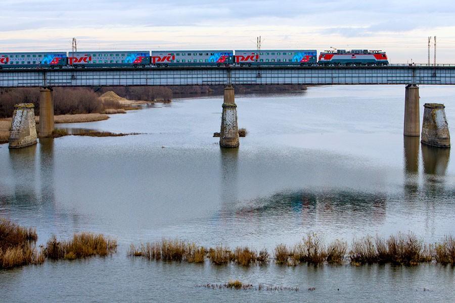 Электропоезд едет через большой мост.